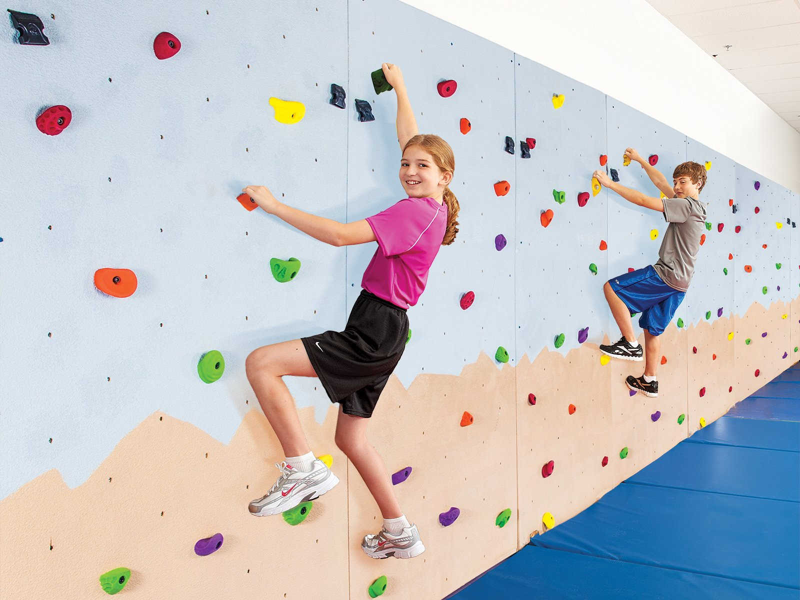 Boy and girl rock climbing indoors