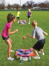Kids playing bean bag toss game