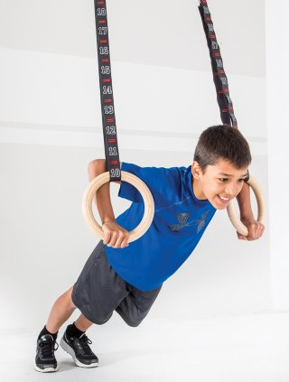 Young boy doing workout on gymnastic rings