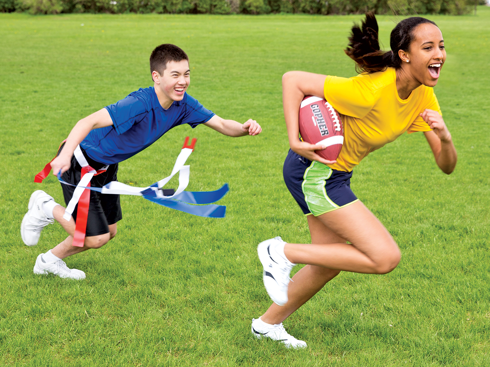 Boy chasing after girl while playing flag football