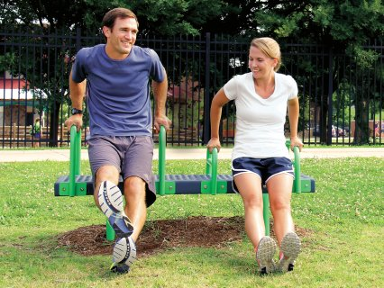 Man and woman doing dip workout station