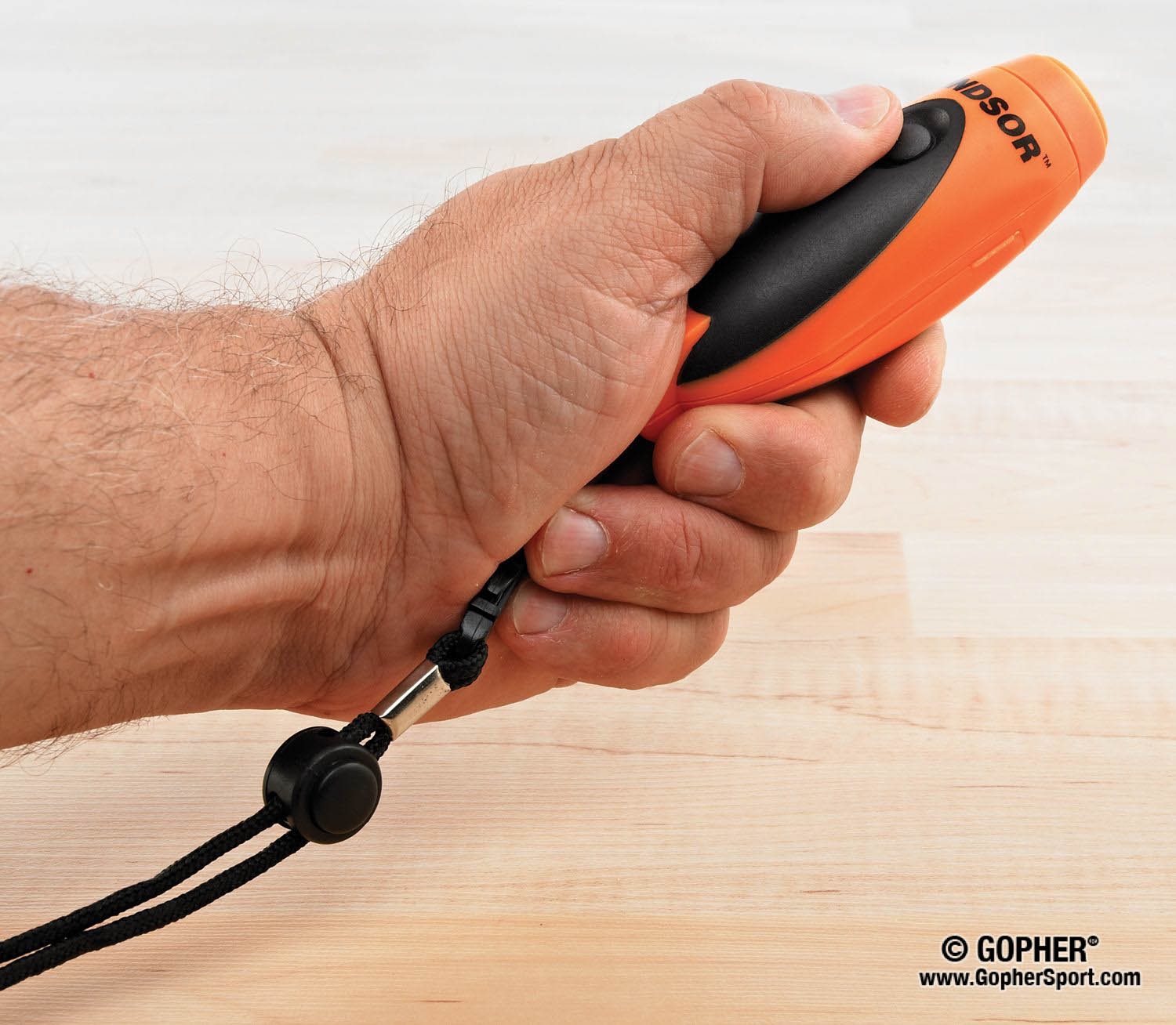 Teacher holding orange electronic whistle