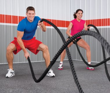 Man and woman working out with conditioning ropes