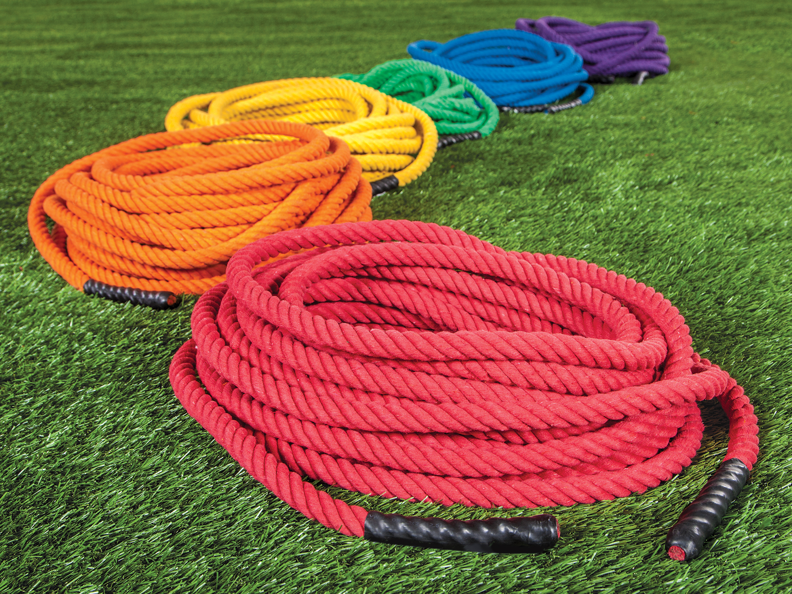 Set of rainbow tug of war ropes in grass