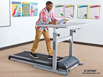 Man reading at desk while working out on treadmill