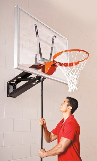 Man changing the height of the basketball hoop