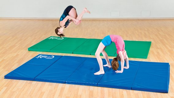 2 girls doing gymnastics activities on foam mats