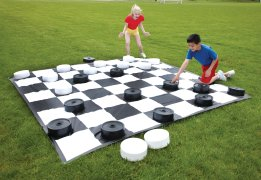 Kids playing with giant checkers board outdoors