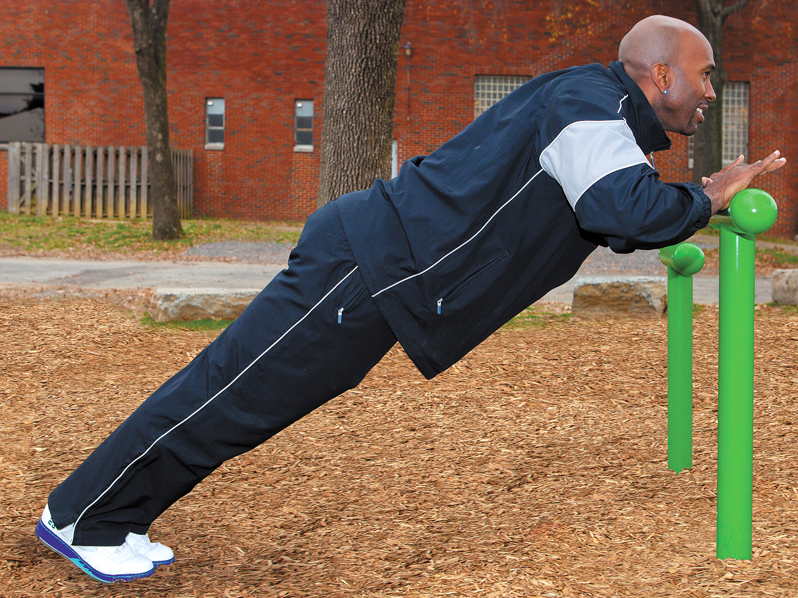People doing push-ups on outdoor fitness equipment