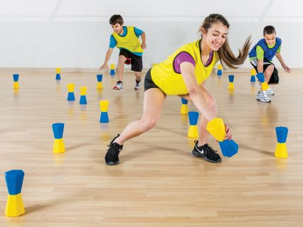 Kids playing with toppletubes in gym class